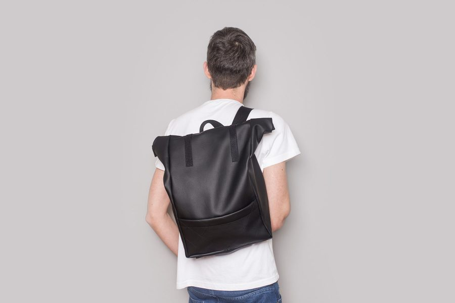 Vegan leather backpack in black on the back of a boy