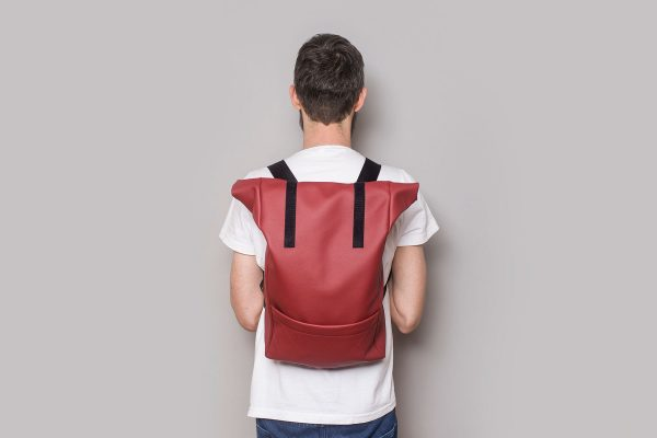 Vegan leather backpack in cherry on the back of a boy