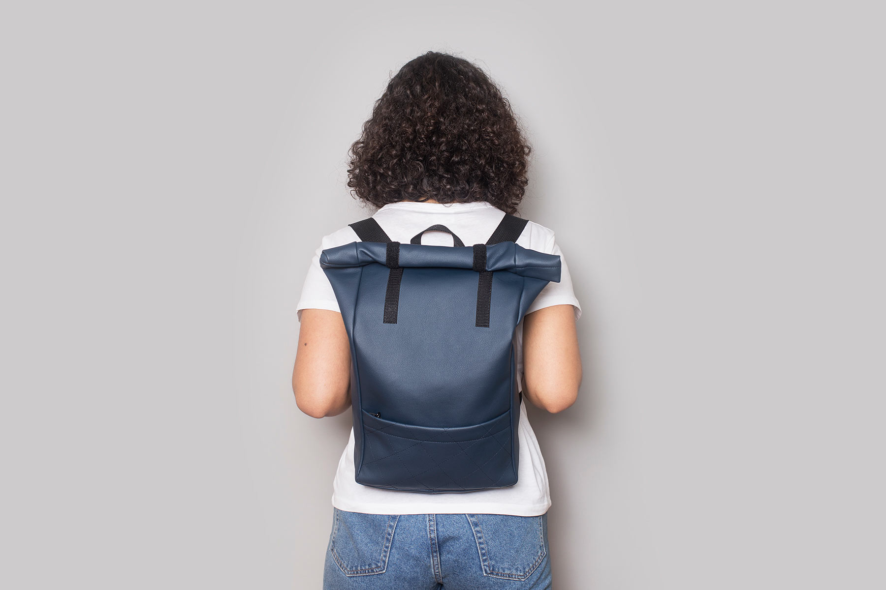 Vegan leather backpack in dark blue on the back of a girl