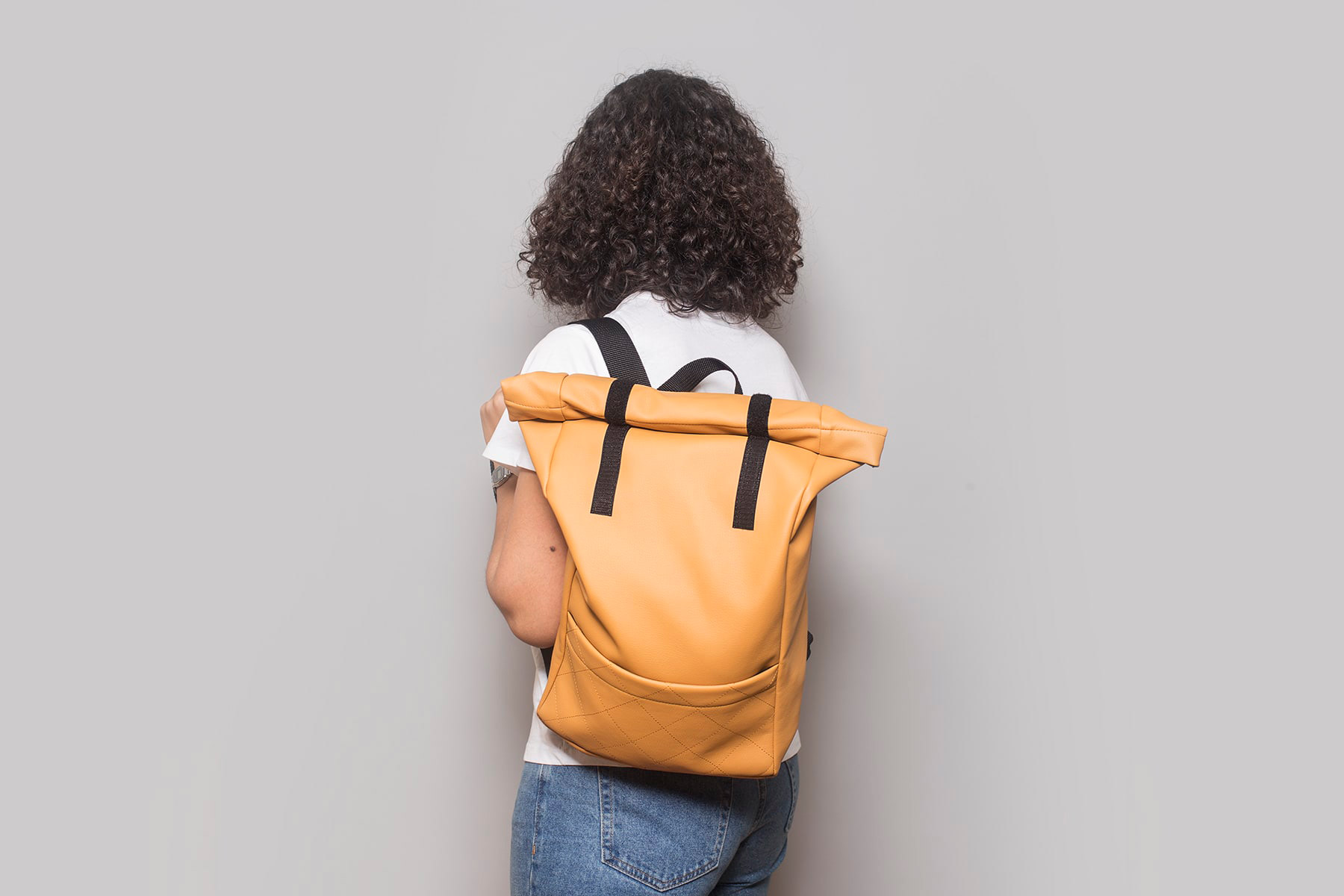 Vegan leather backpack in honey on the back of a girl